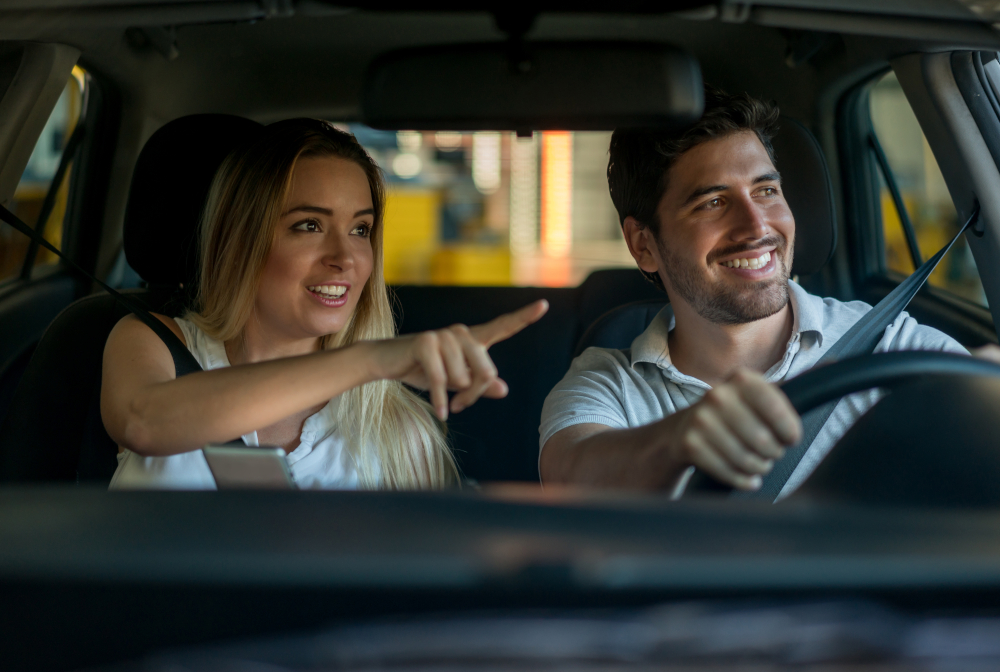Couple Driving And Using A Gps While Pointing Their Way