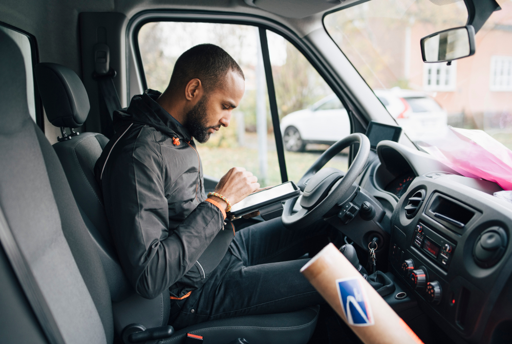 Side View Of Male Worker Using Digital Tablet While Sitting In Delivery Van