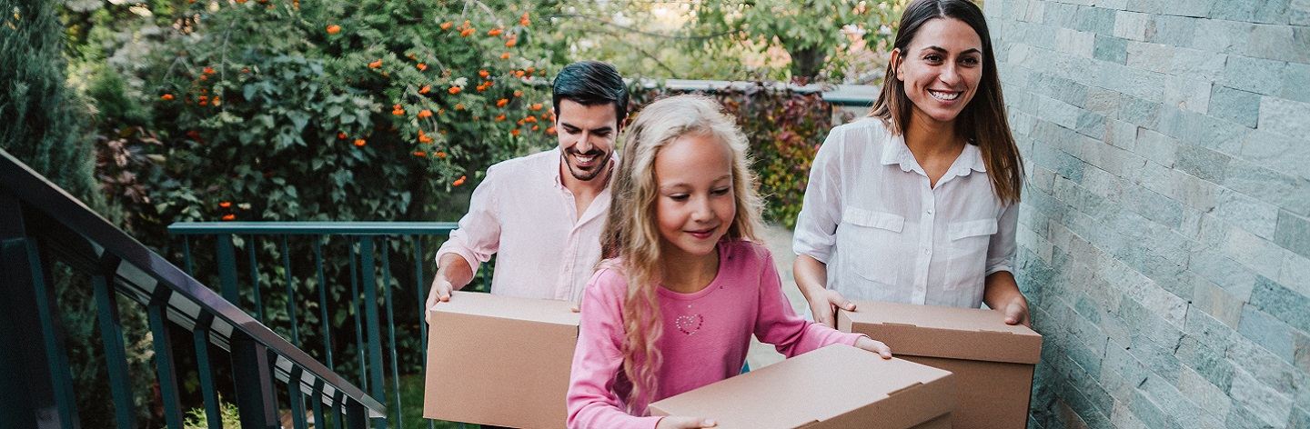 http://Smiling%20Family%20Carrying%20Boxes%20Into%20Their%20New%20House.